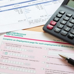 Photo of a UK self assessment tax return with calculator and payslips. The payslip is a mock up the names and all other information on it is fictional.